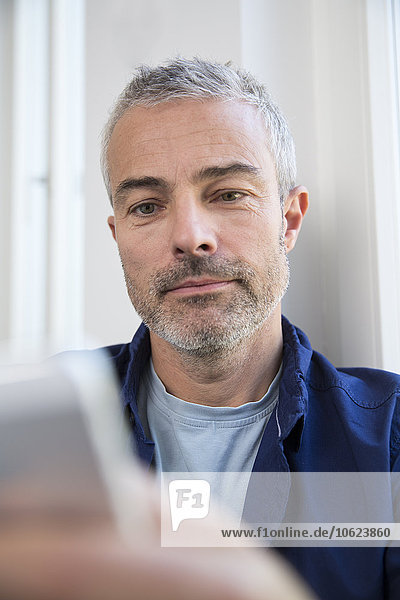 Erwachsener Mann  der von zu Hause aus mit einem digitalen Tablett arbeitet
