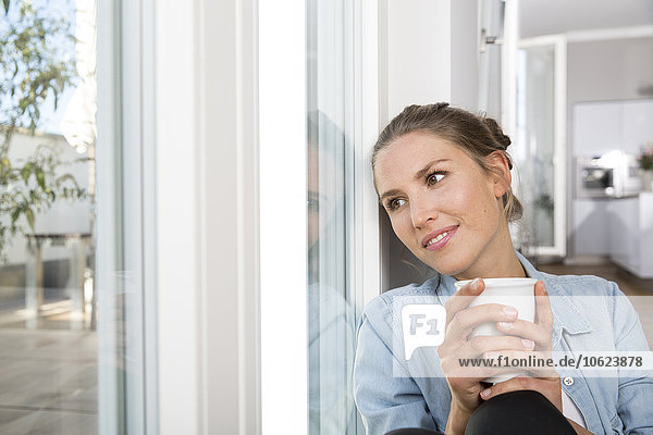 Young woman sitting at the window  drinking coffee
