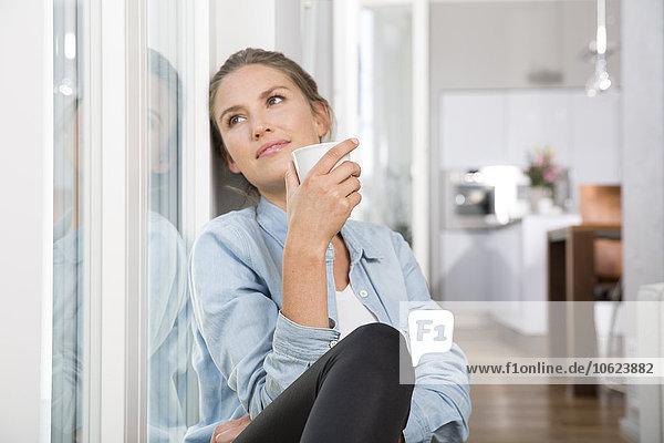 Junge Frau sitzt am Fenster und trinkt Kaffee.