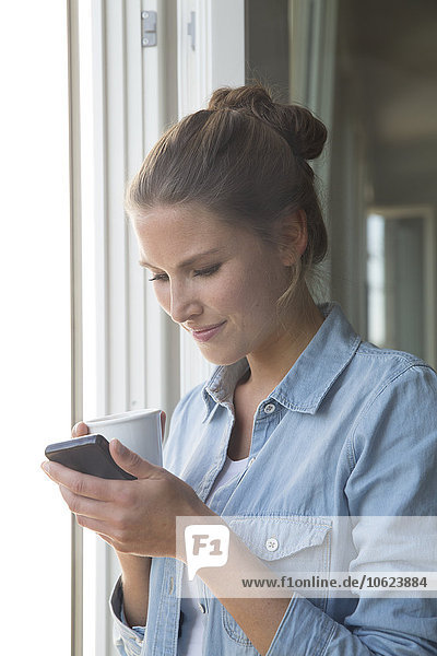 Young woman standing at the window with smart phone and coffee cup