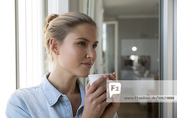 Young woman standing at the window  drinking coffee