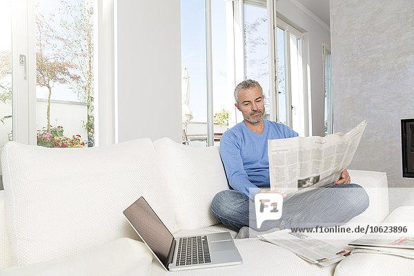 Erwachsener Mann zu Hause  auf der Couch sitzend  Zeitung lesend