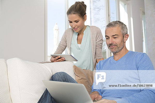 Couple relaxing on couch at home using laptop