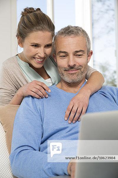 Paar sitzend auf der Couch mit Lapto