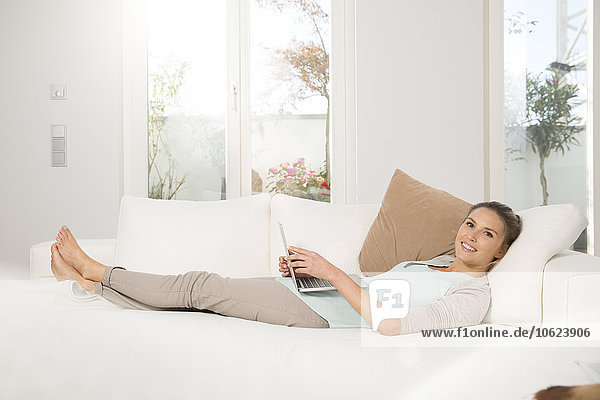 Young woman at home  sitting on couch  using laptop
