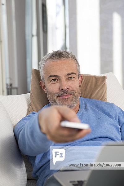 Erwachsener Mann auf der Couch mit Laptop  mit Fernbedienung