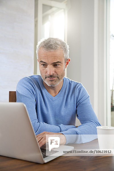 Mature man working from home using laptop