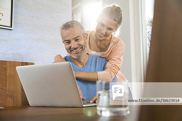 Paar zu Hause arbeiten vom Laptop aus