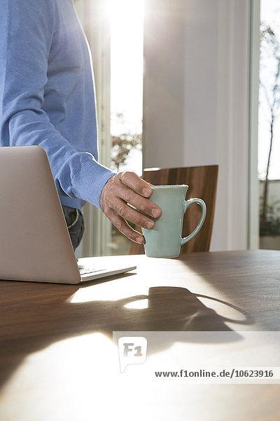 Älterer Mann  der von zu Hause aus arbeitet und den Becher auf den Tisch neben dem Laptop stellt.