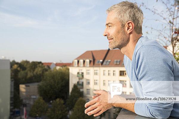 Erwachsener Mann auf dem Balkon  der die Aussicht genießt. Erwachsener Mann auf dem Balkon, der die Aussicht genießt.