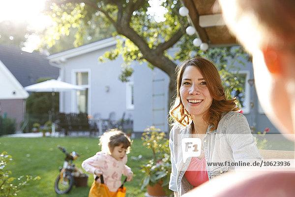 Lächelnde Mutter mit Tochter im Garten