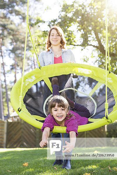 Mutter mit Tochter auf Nestschaukel im Garten