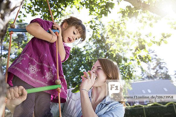 Mutter isst einen Apfel mit Tochter auf Strickleiter im Garten
