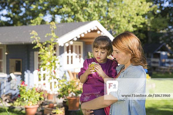 Mutter hält Tochter mit Apfel im Garten