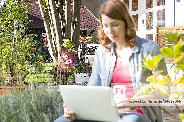 Junge Frau mit Laptop im Garten mit Mutter und Tochter im Hintergrund