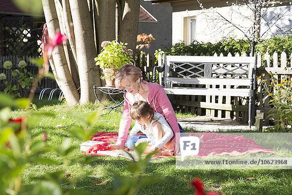 Großmutter mit Enkelin im Garten