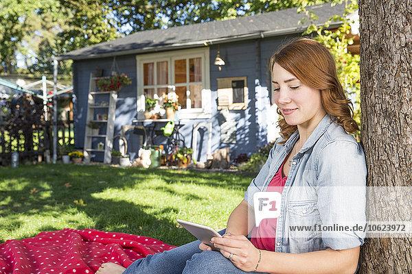 Junge Frau beim Betrachten des digitalen Tabletts im Garten