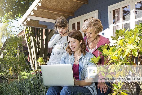Großmutter  Mutter und Tochter beim Blick auf den Laptop auf der Gartenterrasse