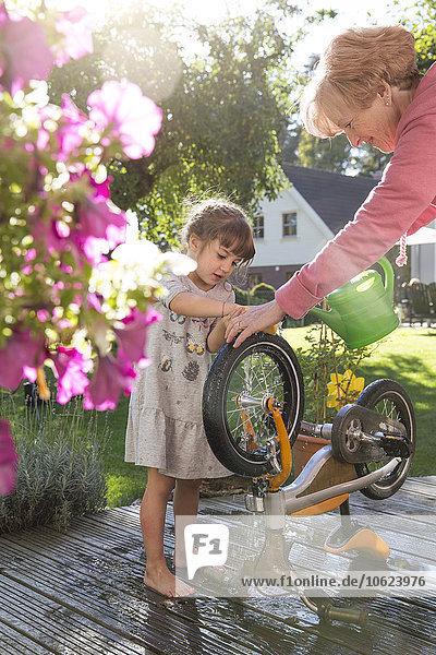 Großmutter und Enkelin waschen Fahrrad auf der Gartenterrasse