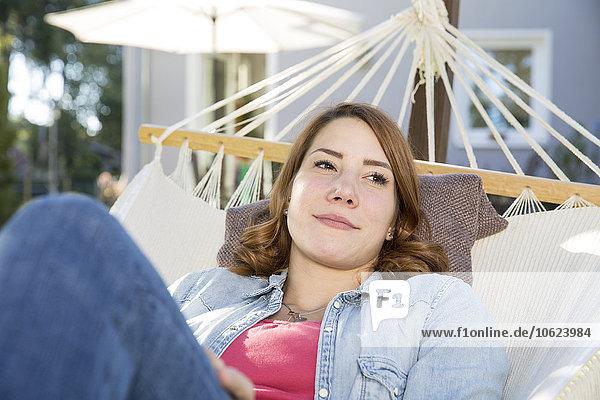 Junge Frau entspannt in der Hängematte im Garten