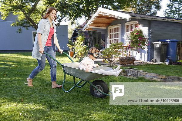 Mutter hat Spaß mit Tochter in Schubkarre im Garten