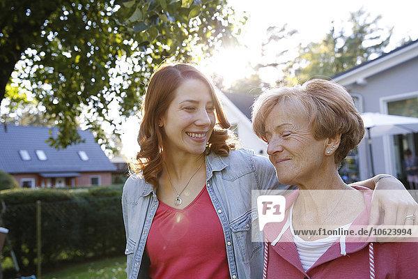 Lächelnde erwachsene Tochter mit älterer Mutter im Garten