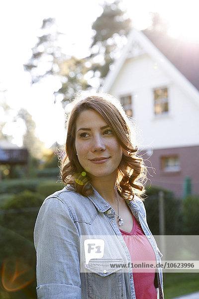 Lächelnde junge Frau im Garten