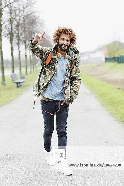 Porträt eines glücklichen Mannes mit gefärbten Ringeln in Camouflage-Jacke