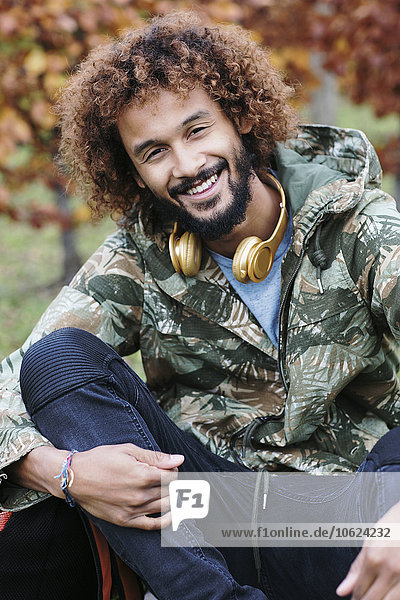 Portrait of man with dyed ringlets wearing camouflage jacket