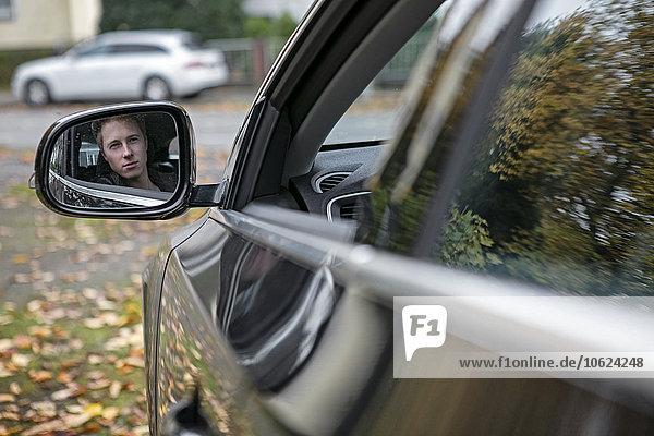 Spiegelung des jungen Mannes im Außenspiegel