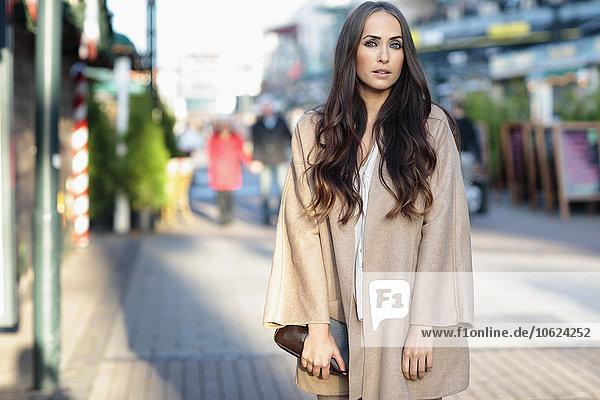 Porträt einer jungen Frau mit langen braunen Haaren in hellbraunem Fell
