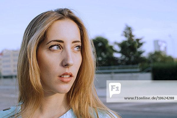 Portrait einer jungen blonden Frau mit Nasenpiercing