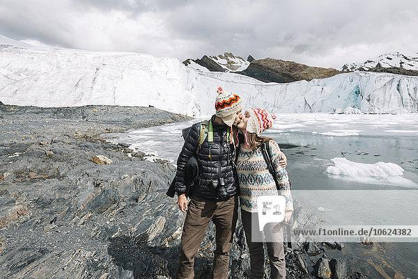 Peru  Paar mit Wollchullos und Küssen vor dem Pastoruri-Gletscher