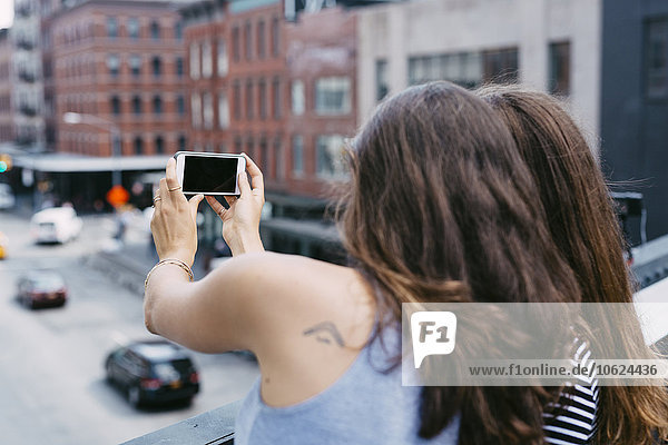 USA  New York City  Freunde  die ein Selfie mit dem Handy nehmen