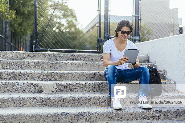 Man sitting on steps using digital tablet