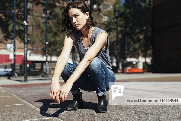 USA  New York City  Manhattan  junge Frau auf einem Spielplatz hockend