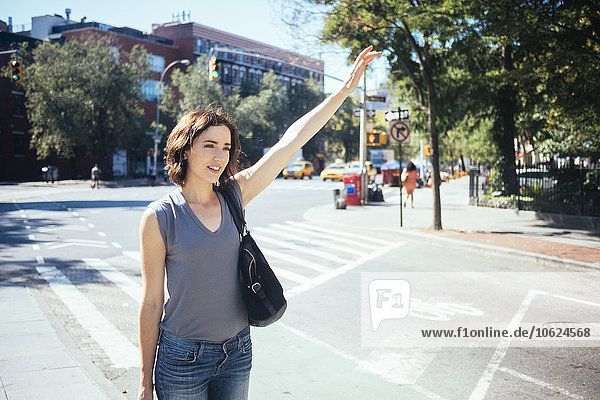 USA  New York City  young woman hailing a taxi