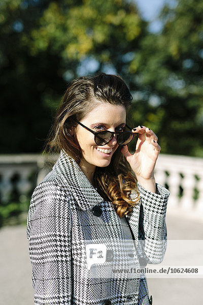 Italy  Vicenza  smiling brunette woman wearing checkered coat and sunglasses