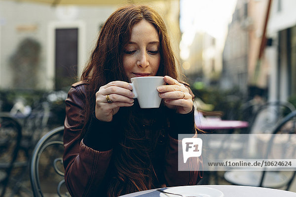 Woman having a coffee outdoors in a little bar