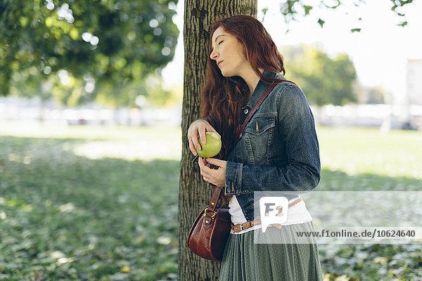 Entspannte Frau mit einem Apfel im Park