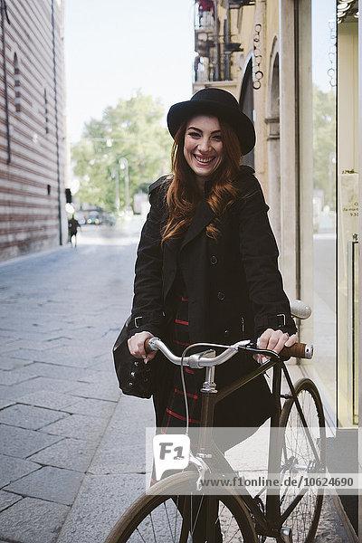 Italien  Verona  glückliche junge Frau mit Fahrrad in der Stadt