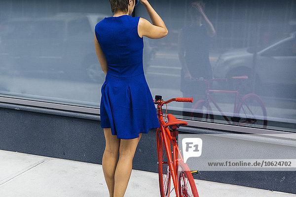 Rückansicht einer Frau im blauen Sommerkleid mit Blick auf ihr Spiegelbild auf einer Glasscheibe