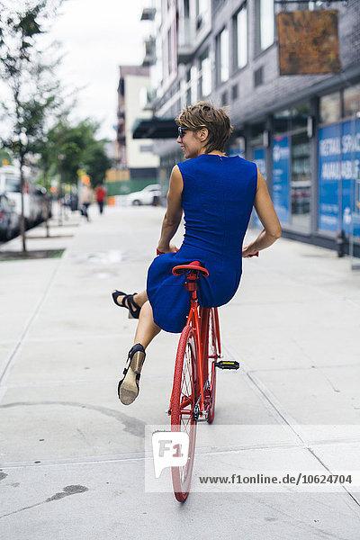 USA  New York City  Williamsburg  Rückansicht einer lächelnden blonden Frau auf rotem Fahrrad