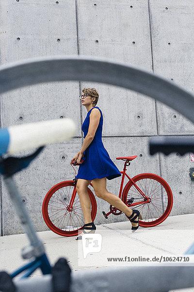 Blonde Frau mit Rennrad auf dem Bürgersteig
