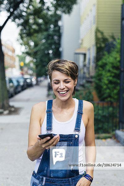 Glückliche blonde Frau in Jeans-Latzhose mit Smartphone