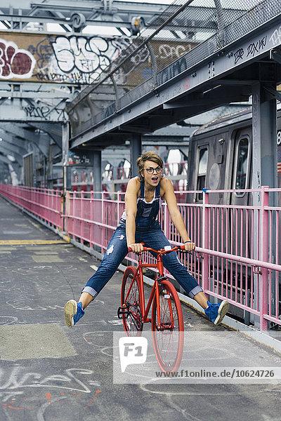 USA  New York City  Williamsburg  Frau mit rotem Rennrad auf der Williamsburg Bridge