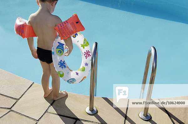 Rückansicht des kleinen Jungen mit schwimmendem Reifen und am Beckenrand stehenden Schwimmflügeln Rückansicht des kleinen Jungen mit schwimmendem Reifen und am Beckenrand stehenden Schwimmflügeln