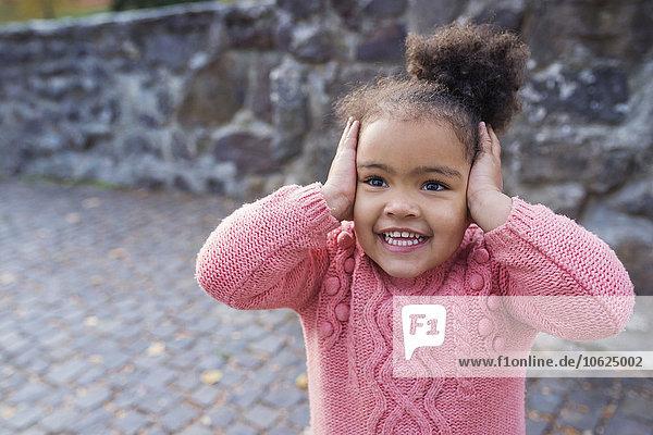 Kleines Mädchen lächelt  Hände über die Ohren Kleines Mädchen lächelt, Hände über die Ohren