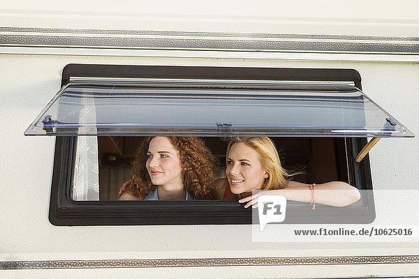 Zwei Freundinnen  die durch das Fenster des Wohnwagens schauen und etwas sehen.