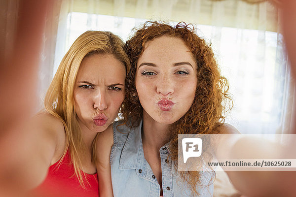 Portrait of two female friends pouting mouths while looking at camera
